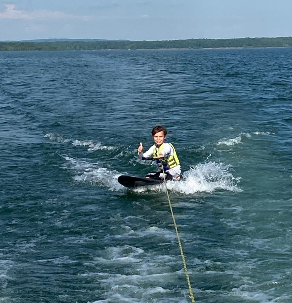 Child knee boarding on the lake