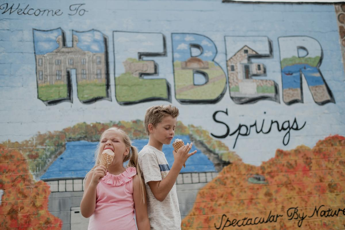 Kids eating ice cream cones in front of mural downtown