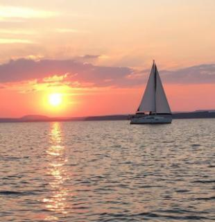 Sunset over water with sailboat in silhouette