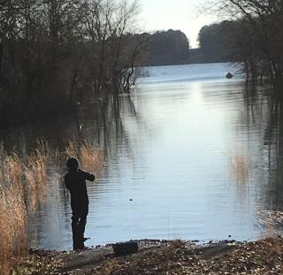 Silhousette of Man fishing on bank of river